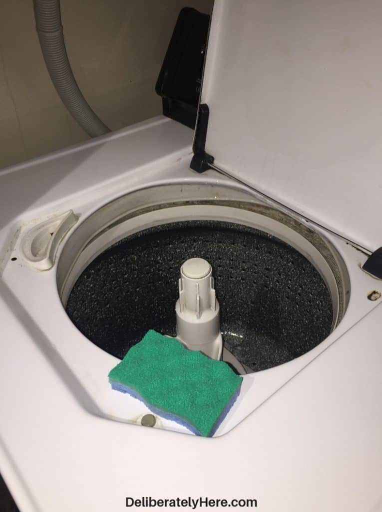 How to clean a top loading washing machine. Scrub the washing barrel
